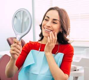 woman admiring new dental veneers in mirror and dentists office